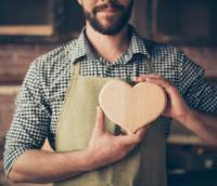 I love my job! Cropped close up photo of happy cheerful joyful carpenter in love, he is showing a heart made of wood